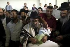 An ultra-Orthodox Jewish man holds his grandson after his circumcision in Neve Ilan near Jerusalem, in this September 24, 2012 file photo. Israel's Tax Authority says it wants its cut of payments traditionally pocketed by practitioners of Jewish ritual circumcisions. REUTERS/Ronen Zvulun/Files