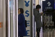 """Люди стоят у пункта обмена валют в Шанхае . Китай может избежать """"жесткого приземления"""", если Пекин проведет реформы госпредприятий и будет придерживаться более рыночно ориентированной и четко сформулированной курсовой политики, сказала в четверг глава Международного валютного фонда Кристин Лагард.  REUTERS/Aly Song"""