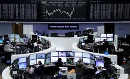 Traders work at their desks in front of the German share price index, DAX board, at the stock exchange in Frankfurt, Germany, February 5, 2016. REUTERS/Staff