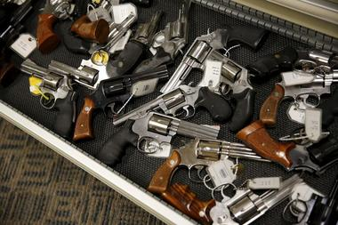 File photo of handguns lining the shelves in the gun library at the U.S....