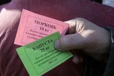 Продуктовые карточки с правом льготного приобретения овощей. Высоковск, 2 ноября 2007 года. Минпромторг подготовил схему адресной продовольственной помощи населению, продолжающему беднеть из-за кризиса, согласно которой малообеспеченные россияне получат электронные карты для покупки еды в магазинах. REUTERS/Alexander Natruskin