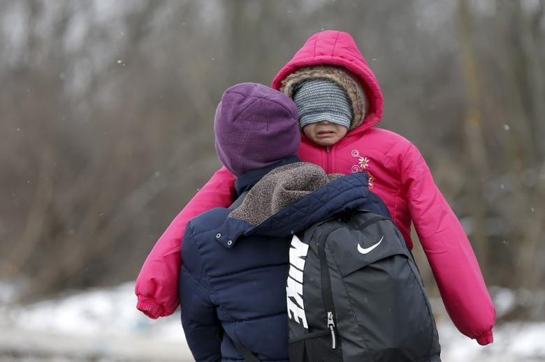 A migrant carries a child as they walk through a frozen field after crossing the border from Macedonia, near the village of Miratovac, Serbia, January 18, 2016. REUTERS/Marko Djurica