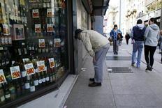 Una persona mira los precios de los productos de una tienda desde la calle, en el centro de Santiago, Chile. 26 de agosto de 2014. El Indice de Precios al Consumidor (IPC) en Chile subió un 0,5 por ciento en enero, más de lo esperado por el mercado, impulsado por alzas en bienes y servicios, así como en bebidas alcohólicas y tabaco, mostraron datos difundidos el lunes por el Gobierno. REUTERS/Ivan Alvarado