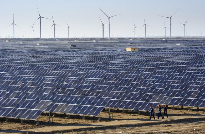 Workers walk past solar panels and wind turbines (rear) at a newly-built power plant in Hami, Xinjiang Uighur Autonomous Region, China, September 17, 2015.  REUTERS/Stringer