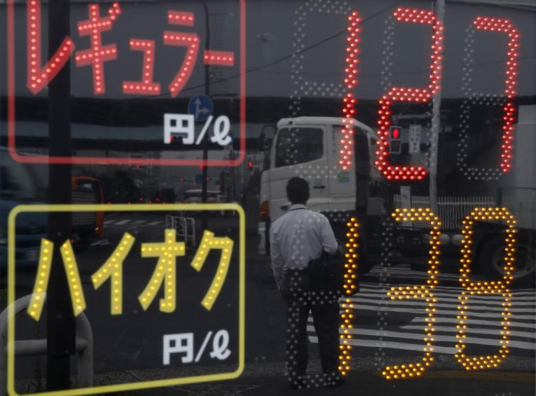 A man and vehicles are reflected in a price display at a gas station in Tokyo August 26, 2015. REUTERS/Toru Hanai