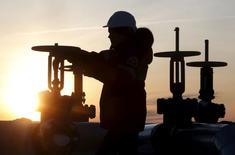 Рабочий проверяет вентиль нефтепровода на месторождении Имилорское рядом с Когалымом. Цены на нефть снижаются за счет опасений за рост мировой экономики и рекордных запасов нефти на терминале в американском Кушинге. REUTERS/Sergei Karpukhin