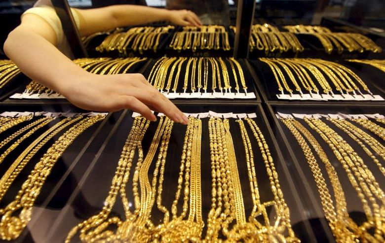 An employee arranges gold jewellery in the counter as her arm is reflected in the mirror at a gold shop in Wuhan, Hubei province, in August 25, 2011 file photo. REUTERS/Stringer/Files