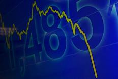 График индекса Hang Seng на экране в брокерской конторе в Гонконге. 8 июля 2015 года. Ключевой индекс Гонконга снизился до минимального на момент закрытия уровня за три с половиной года в пятницу из-за бегства от риска инвесторов, напуганных мировым падением банковских акций, и из-за опасений о глобальной экономике, особенно о Китае. REUTERS/Tyrone Siu