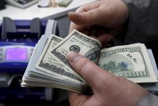Un cajero contando dólares en una casa de cambios en Estambul, abr 15, 2015. El dólar subía el viernes, luego de un dato que mostró que el  gasto del consumidor estadounidense cobró impulso en enero, lo que respalda la posibilidad de que la Reserva Federal suba las tasas de interés este año.   REUTERS/Murad Sezer