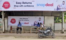 Commuters sit at a bus stop adorned with an advertisement of Indian online marketplace Snapdeal featuring actor Aamir Khan, in Bengaluru, India, October 15, 2015. REUTERS/Abhishek Chinnappa