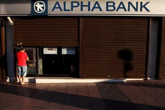 man withdraws money at an Alpha Bank branch ATM in central Athens ...