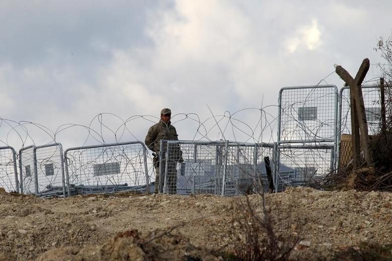 A Turkish soldier standing guard is seen from the Syrian town of Khirbet Al-Joz at the Turkish-Syrian border, in Latakia countryside, where internally displaced Syrian people are waiting to get permission to cross into Turkey, February 7, 2016. REUTERS/Ammar Abdullah