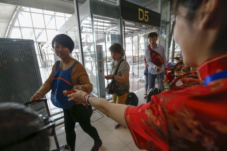 Chinese tourists receive souvenirs from airport officers as part of the Chinese Lunar New Year celebrations at Bangkok's Suvarnabhumi Airport, Thailand, February 5, 2016. REUTERS/Athit Perawongmetha