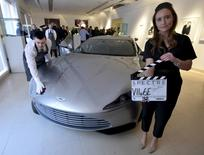 "An employee poses as an Aston Martin DB10, one of the series of DB10s designed and engineered by Aston Martin for the James Bond film ""Spectre"", is polished during a media preview of ""Spectre - the Auction"", at Christie's auction house in London February 15, 2016. REUTERS/Hannah McKay"