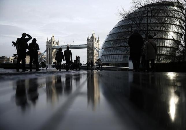 Pedestrians walk near City Hall and Tower Bridge in London, Britain January 24, 2016.    REUTERS/Neil Hall