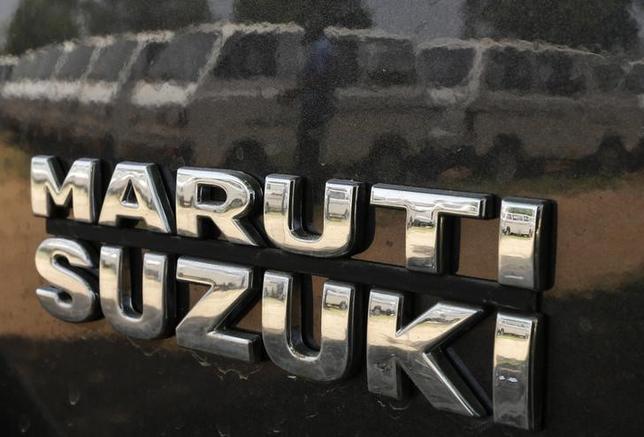2月21日、スズキのインド子会社マルチ・スズキは、同日午後から2工場の操業を一時中止すると発表。写真はインドのアフマダーバードで、同子会社製自動車のボディに映る男性。2014年5月撮影(2016年 ロイター/Amit Dave)