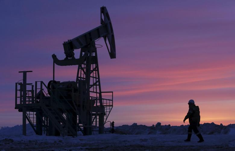A worker walks past a pump jack on an oil field owned by Bashneft company near the village of Nikolo-Berezovka, northwest from Ufa, Bashkortostan, Russia, in this January 28, 2015 file photo. REUTERS/Sergei Karpukhin/Files