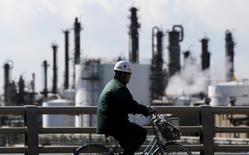 En la imagen, un trabajador en bicicleta pasa cerca a una fábrica en la zona industrial de Keihin en Kawasaki, Japón. 17 de febrero, 2016. La mayoría de las empresas japonesas sólo planea un incremento modesto de los salarios este año, según un sondeo de Reuters, en momentos en que las DÉBILES perspectivas de crecimiento y unos mercados agitados las llevan a resistir las demandas del primer ministro, Shinzo Abe, de unas alzas robustas. REUTERS/Toru Hanai