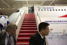 Visitors walk past a model of the C919 aircraft, presented by Commercial Aircraft Corporation of China,Ltd. (COMAC) during the 49th Paris Air Show at the Le Bourget airport near Paris, in this file photo dated June 20, 2011. REUTERS/Pascal Rossignol