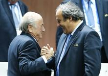 UEFA President Michel Platini (R) congratulates FIFA President Sepp Blatter after he was re-elected at the 65th FIFA Congress in Zurich, Switzerland, May 29, 2015. Sepp Blatter has been re-elected as FIFA president for a fifth term after Jordan's Prince Ali bin Al Hussein conceded defeat at the Congress of world football's governing body on Friday. REUTERS/Arnd Wiegmann
