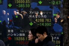 Люди проходят мимо экрана с показателями индексов в Токио 10 февраля 2016 года. Японский индекс Nikkei закрылся в пятницу наибольшим повышением за последние три недели после того, как склонность инвесторов к риску восстановилась на фоне неуклонно слабеющей иены и ночному подъёму на Уолл-стрит. REUTERS/Thomas Peter