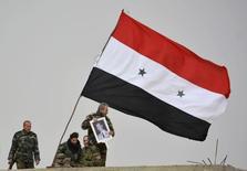 Лояльные Башару Асаду военные с его портретом и флагом Сирии в Дейр аль-Адасе к югу от Дамаска 10 февраля 2015 года. Переговоры о мире в Сирии между режимом Башара Асада и его противниками могут возобновиться в Женеве 7 марта, сообщил чиновник российского МИДа на фоне международных усилий обеспечить согласованное Вашингтоном и Москвой перемирие. REUTERS/Stringer