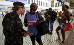 A Brazilian Army soldier distributes pamphlets with information to combat the Aedes aegypti mosquito during the National Day of Mobilization Zika Zero at Central train station in Rio de Janeiro, Brazil, February 13, 2016.   REUTERS/Sergio Moraes