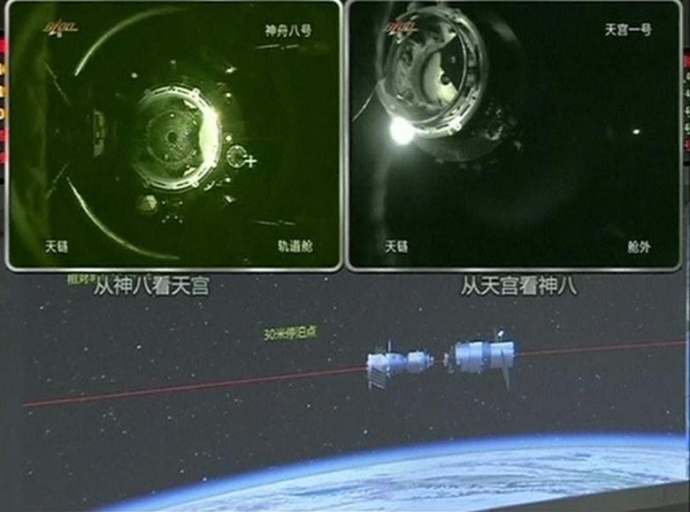 A view of China's Tiangong (Heavenly Palace) 1 module (top L) just before it docks with the Shenzhou 8 spacecraft (top R) is seen on a monitoring screen showing a computer animation (bottom) of the docking process at the Beijing Aerospace Flight Control Center November 3, 2011. REUTERS/CCTV via Reuters TV