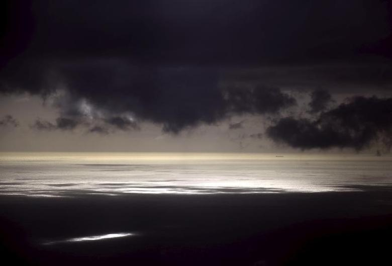 Storm clouds can be seen above a coal ship as it sails near Lady Elliot Island located north-east of the town of Bundaberg in Queensland, Australia, June 9, 2015.  REUTERS/David Gray
