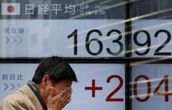 Un peatón pasa frente a un tablero electrónico que muestra el índice Nikkei, afuera de una correduría en Tokio, Japón, 29 de febrero de 2016. Las acciones japonesas cayeron el lunes por la fortaleza del yen frente al dólar y luego de que la confianza de los inversores se vio afectada por un retroceso en las acciones chinas. REUTERS/Yuya Shino