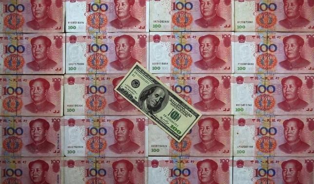 2月29日、中国が、上海で開かれたG20から間を置かず追加緩和に踏み切った。写真は人民元とドルの紙幣。北京で2013年5月撮影(2016年 ロイター/Petar Kujundzic)