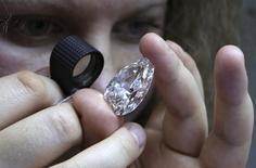 Сотрудница одной из компаний, принадлежащих Алросе, изучает алмаз в Москве 17 октября 2013 года. Российское правительство может пойти на приватизацию 10,9 или 18,9 процента акций алмазной монополии Алроса, сказал во вторник министр экономического развития Алексей Улюкаев. REUTERS/Sergei Karpukhin