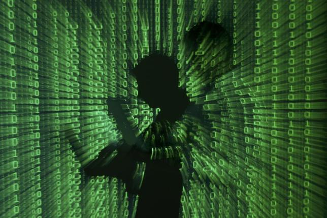 An illustration picture shows a projection of binary code on a man holding a laptop computer, in an office in Warsaw, in this file photograph dated June 24, 2013. REUTERS/Kacper Pempel/files