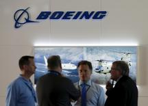 Visitors talk outside a Boeing booth during the opening day of the Singapore Airshow at Changi Exhibition Center February 16, 2016.  REUTERS/Edgar Su