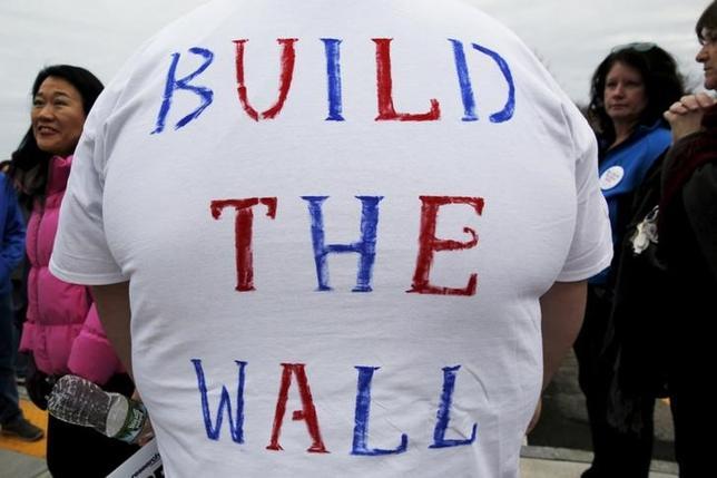 3月1日、犯罪組織の暴力と貧困が、過去数年にわたりメキシコ人や中米諸国の人々を米国へと向かわせたが、最近では新たなけん引役が浮上。トランプ氏の反移民キャンペーンだ。写真は「壁を造れ」と書かれたTシャツを着る同氏の支持者。米ニューハンプシャー州で2月4日撮影(2016年 ロイター/Brian Snyder)