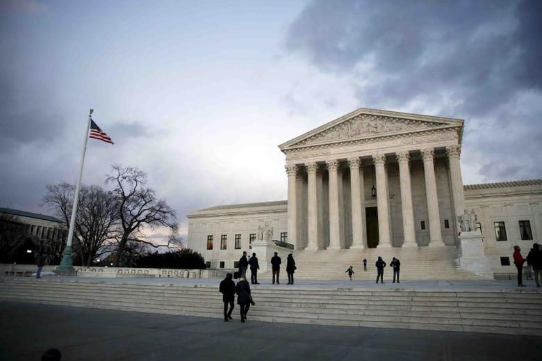 People stand outside the Supreme Court building at Capitol Hill in Washington D.C., in this February 13, 2016 photo. REUTERS/Carlos Barria