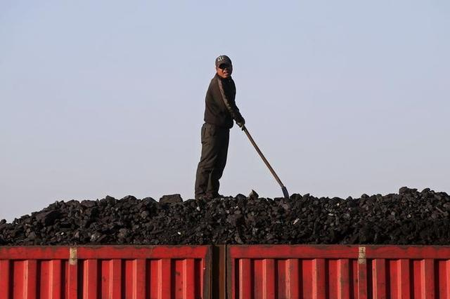 A worker speaks as he loads coal on a truck at a depot near a coal mine from the state-owned Longmay Group on the outskirts of Jixi, in Heilongjiang province, China, October 24, 2015. REUTERS/Jason Lee