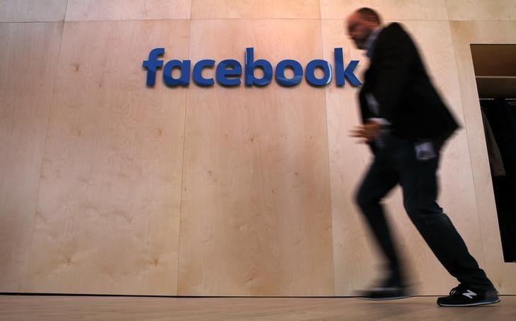 A man walks in front of the Facebook logo at the new Facebook Innovation Hub during a preview media tour in Berlin, Germany, February 24, 2016.  REUTERS/Fabrizio Bensch/Files