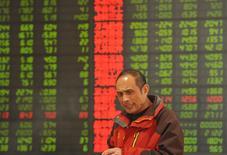 Un inversor frente a un tablero electrónico que muestra información bursátil, en una correduría en Fuyang, China. 29 de febrero de 2016. Las acciones chinas cayeron en torno a un 2 por ciento el jueves, lideradas por los títulos bancarios y del sector energético, luego de que los inversores interpretaron unos datos que mostraron que la inflación se aceleró en febrero como algo negativo para la economía. REUTERS/China Daily