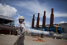 Foto de archivo de un trabajador caminando junto a una instalación petrolera operada por PDVSA, en Morichal, Venezuela. 28 de julio de 2011. Los precios del crudo podrían bajar en 10 dólares por barril y borrar las alzas recientes si los países dentro y fuera de la OPEP no logran acordar un plan para congelar los niveles de producción, estimó el jueves la correduría noruega DNB Markets. REUTERS/Carlos Garcia Rawlins/Files