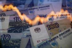 График на фоне рублевых купюр. Варшава, 7 ноября 2014 года. Рубль вечером четверга растерял преимущество после обновления максимумов текущего года в ответ на решение ЕЦБ довести уровень ключевой процентной ставки до нулевой отметки и расширить программу денежного стимулирования, что предполагает снижение стоимости фондирования операций с высокорискованными активами для европейских инвесторов. REUTERS/Kacper Pempel