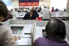 Инвесторы в брокерской конторе в Шанхае. 7 марта 2016 года. Китайские акции завершили пятничные торги небольшим повышением, сумев сменить динамику по ходу сессии благодаря банковскому сектору. REUTERS/Aly Song