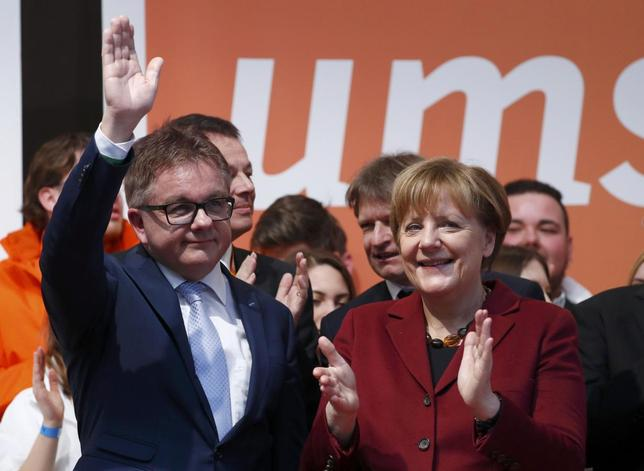 Angela Merkel German Chancellor and leader of the conservative Christian Democratic Union (CDU) party applauds Guido Wolf  (L) the CDU's Baden-Wuerttemberg top candidate, after a final campaign rally Haigerloch, south-western Germany March 12, 2016, ahead of Sunday's three regional state elections where the refugee crisis is expected to dominate voters' decisions. REUTERS/Kai Pfaffenbach