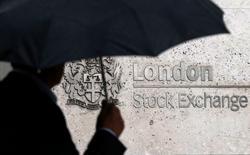 Человек с зонтом проходит мимо здания Лондонской фондовой биржи 24 августа 2015 года. Немецкая биржа Deutsche Boerse и Лондонская фондовая биржа (LSE) договорились о слиянии стоимостью $30 миллиардов, которое приведёт к созданию крупнейшего европейского биржевого оператора, способного конкурировать с США.  REUTERS/Suzanne Plunkett