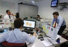 El Tesoro Público colocó el jueves bonos y obligaciones por importe de 2.858 millones de euros, en la primera subasta a medio y largo plazo tras las nuevas medidas de estímulo aprobadas por el BCE la semana pasada. En esta imagen de archivo, operadores miran sus ordernadores durante una subasta de bonos españoles en Madrid, el 5 de diciembre de 2012. REUTERS/Andrea Comas