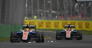 Manor Racing F1 driver Rio Haryanto throws up sparks in front of team mate Pascal Wehrlein during the first practice session at the Australian Formula One Grand Prix in Melbourne.   REUTERS/Jason Reed