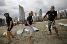 (L-R) Edmea Pereira, 69, Elsa Rodrigues, 61, and Osmidio Conde, 71, take part in their surf class in Santos, Sao Paulo state, Brazil, March 16, 2016. REUTERS/Nacho Doce