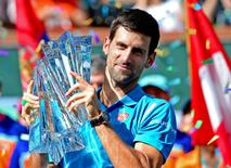 Mar 20, 2016; Indian Wells, CA, USA; Novak Djokovic (SRB) holds his trophy after defeating Milos Raonic (not pictured) in the men's final match in the BNP Paribas Open at the Indian Wells Tennis Garden. Djokovic won 6-2, 6-0. Mandatory Credit: Jayne Kamin-Oncea-USA TODAY Sports