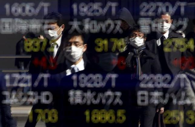 Pedestrians wearing masks are reflected in an electronic board showing various stock prices outside a brokerage in Tokyo, Japan, February 26, 2016.  REUTERS/Yuya Shino
