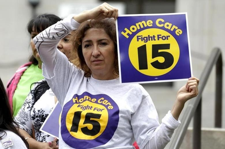 Ingrid Alarcon holds a sign before the Los Angeles City Council approved a proposal to increase the minimum wage to $15.00 per hour in Los Angeles, California June 3, 2015. REUTERS/Jonathan Alcorn
